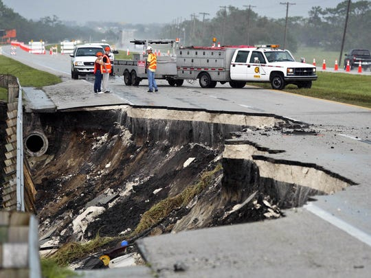 Department of Transportation workers stand near a hole in State Road 60 near Lake Wales in Polk County on Aug. 14, 2004. A man was killed when his car plunged into the hole the night before during Hurricane Charley.