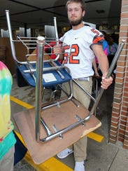 Plymouth's Tyle Luedke waits in line with a desk to