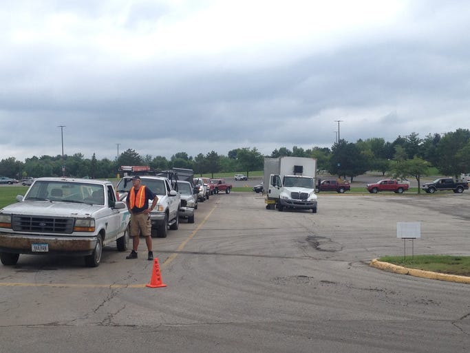 Vehicles line up for the Mega SCRUB event at Southridge Mall, 1111 E Army Post Road in Des Moines, Saturday.