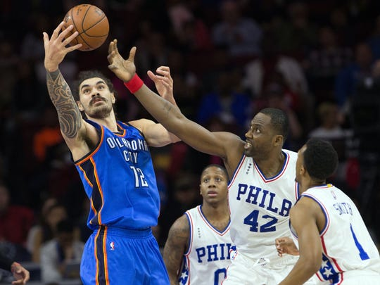 Thunder center Steven Adams (72) reaches for a loose ball against 76ers forward Elton Brand (42).