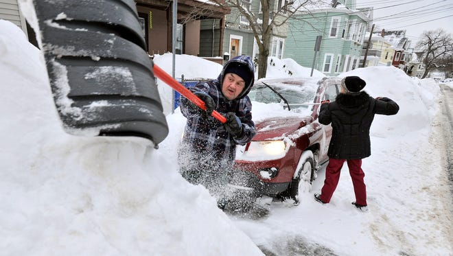 Rich and Kathy Melvin shovel out their car in front of their house in Somerville, Mass., on Feb. 10, 2015.