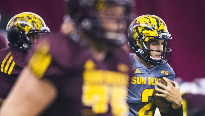 ASU quarterback Mike Bercovici, right, runs with the ball during warmups in the Verde Dickey Dome at practice, Tuesday morning, August 18, 2015.