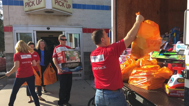 About 50 Health First employees spent Thursday morning buying and loading gifts at Toys R Us for needy children in the area. The toys will go 600 children in the area and is part of an outreach program of the South Brevard Sharing Center.