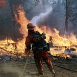 A firefighter hoses down hot spots during a controlled burn to fight the King fire on Monday, Sept. 22, 2014, near Placerville, Calif.