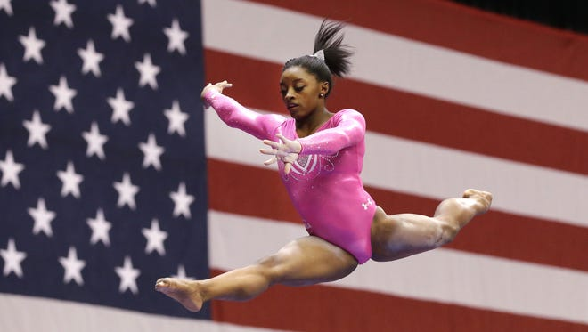 Simone Biles jumps off the balance beam during the American Cup gymnastics competition Saturday, March 7, 2015, in Arlington, Texas.