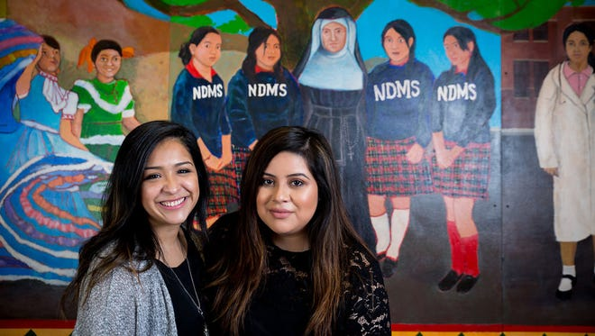 Crystal Serna (left) and Christian Oliva, staff members at Notre Dame School of Milwaukee, stand in front of a mural from their 2007 graduating class. They are depicted in the mural on the nun's right.