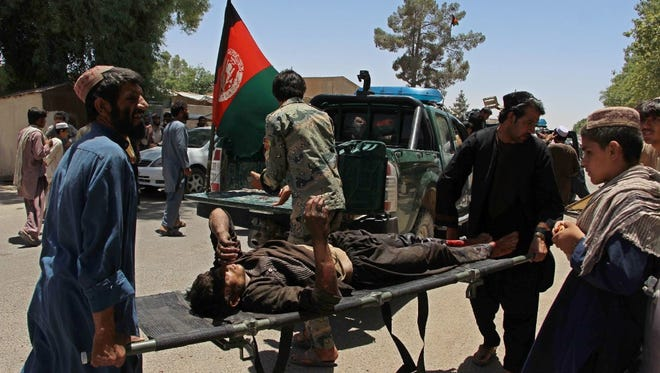 Afghan men carry a victim of a powerful car bomb in Lashkar Gah, the capital of Helmand province, on June 22, 2017.