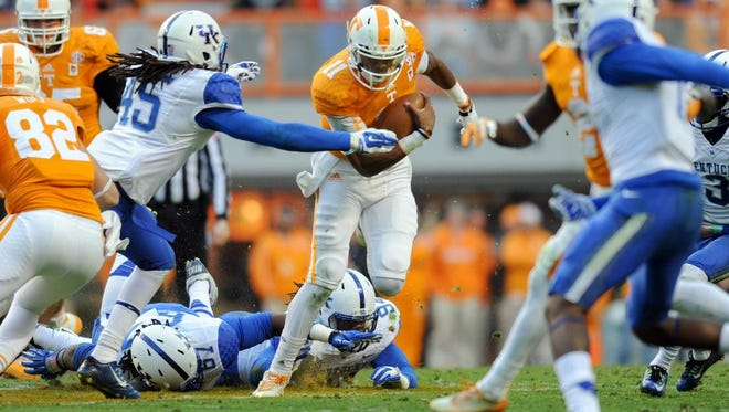 Nov 15, 2014; Knoxville, TN, USA; Tennessee Volunteers quarterback Joshua Dobbs (11) runs the ball against the Kentucky Wildcats during the first half at Neyland Stadium.