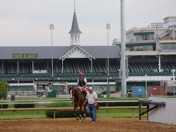 California Chrome comes off the track at Churchill Downs with exercise rider William Delgado, and assistant trainer Alan Sherman. May 8, 2014