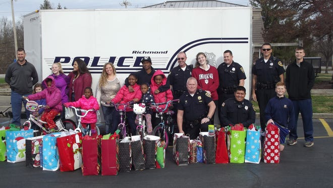 Richmond police personnel and their families present Christmas gifts to the family of an accident victim.