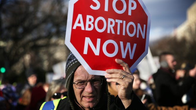 A pro-life activist holds a sign as he participates in the annual March for Life January 22, 2015 in Washington, DC. Pro-life activists gathered in the nation's capital to mark the 1973 Supreme Court  Roe v. Wade decision that legalized abortion.