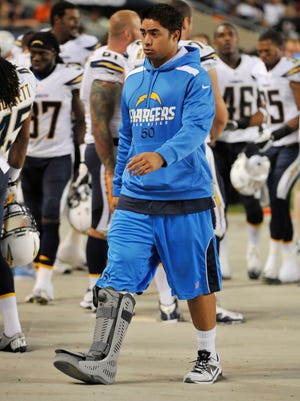 Manti Te'o walks the sidelines with a boot on his right leg during a preseason game last month.