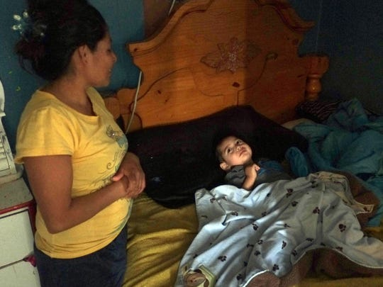 Reyna Melgar stands beside the bed of her son Josue in her trailer in Thermal on January 29, 2014. Josue has a debilitating neurological disease.