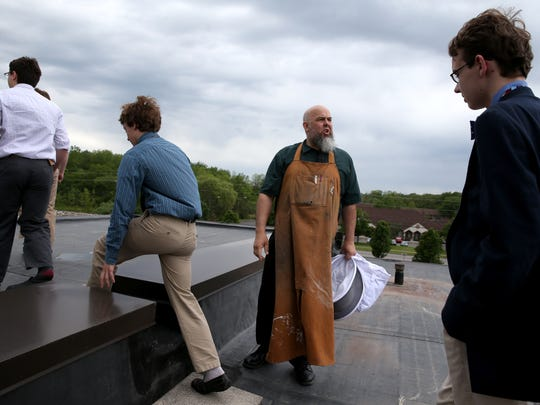 Greg Lendeck leads students to the roof of McQuaid