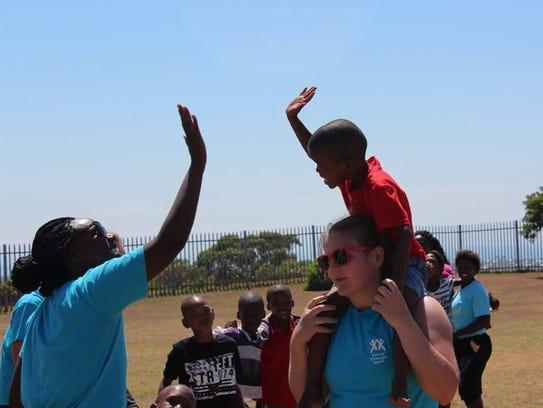 Cape Henlopen grad Domineque Scott high fives a child