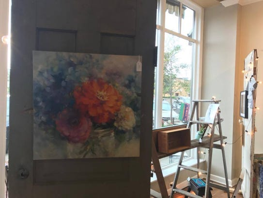 A flower painting by Nancy Laliberte hangs in The Local