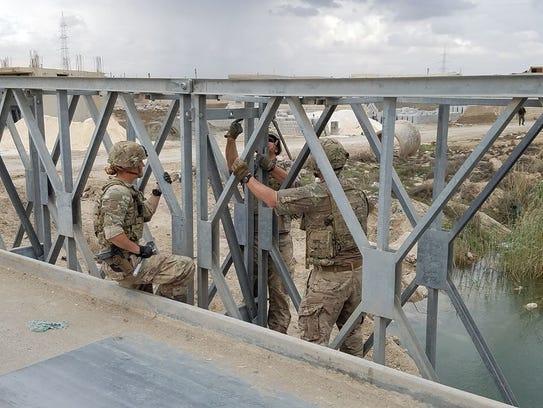 Rosberg works on a bridge alongside Staff Sergeant