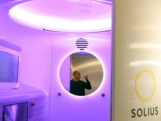 Kyle Diercks, chief revenue officer of Solius, is reflected in the mirror of the company's machine on Bainbridge Island.