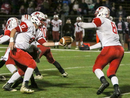Point Beach QB Luke Frauenheim (left) hands off to John Nista (8) against Bound Brook in the Central Group I semifinals on Friday, Nov. 17, 2017.