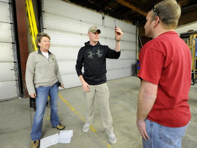 New Palestine police officer Dillon Silver, center, asks volunteer J.R. Corman, right, to follow the movement of a pen as instructor Lt. Bridget Foy looks on during a field sobriety test training, Sunday, March 9, 2014, at the Fortville Police Department.