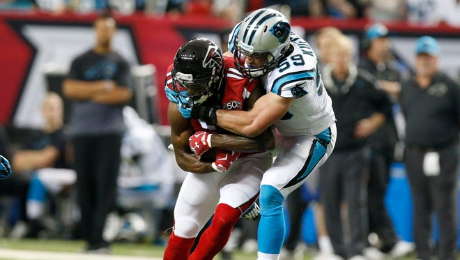 Carolina Panthers linebacker Luke Kuechly tackles Atlanta Falcons wide receiver Julio Jones (11) after a catch in the first quarter at the Georgia Dome.