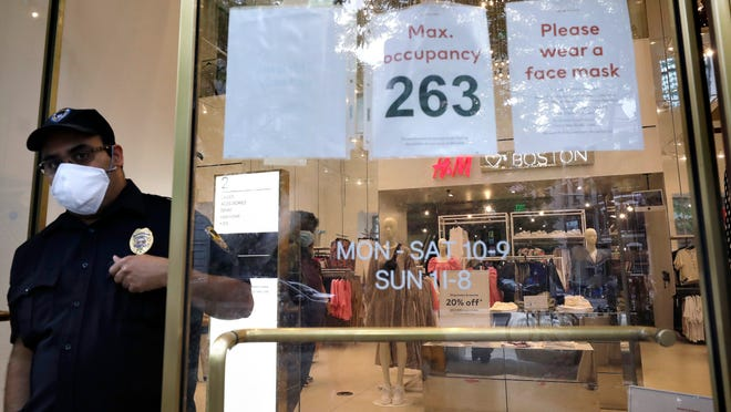 A signs at the entrance to a clothing store requests that customers wear a mask out of concern for the coronavirus, Sunday, June 28, 2020, in Boston. Under step two in phase two of the state's plan to reopen the economy during the coronavirus pandemic, beginning June 22, 2020 clothing stores are allowed to offer the use of dressing rooms, by appointment only.