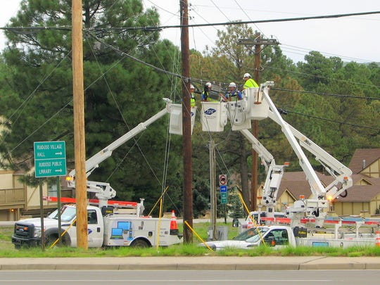 This image raises the age-old question about a light bulb. Workers with TDS Telecom internet, television and phone service provider, look like the body of a mechanical spider as they confer on a connection problem in Ruidoso.