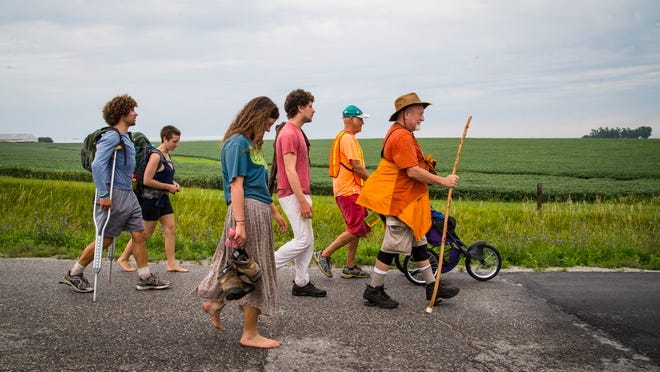 Climate march participants start the day Tuesday on a road east of Atlantic on the way to Cumberland, Ia. The group is   walking across the country to raise awareness of climate-change issues.