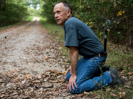 Scott Ballard kneels down close to a small Cottonmouth snake along Snake Road to demonstrate that these types of snake aren't aggressive unless directly provoked on Tuesday, Oct. 3, 2017. Cottonmouths, also known as Water Moccasins, are venomous but they rarely bite humans unless they are stepped on or played with.