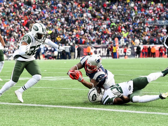 New England Patriots running back Dion Lewis (33) dives for a touchdown against the New York Jets during the first half at Gillette Stadium.