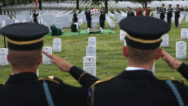 Soldiers salute as a casket is carried to a gravesite at Arlington National Cemetery,