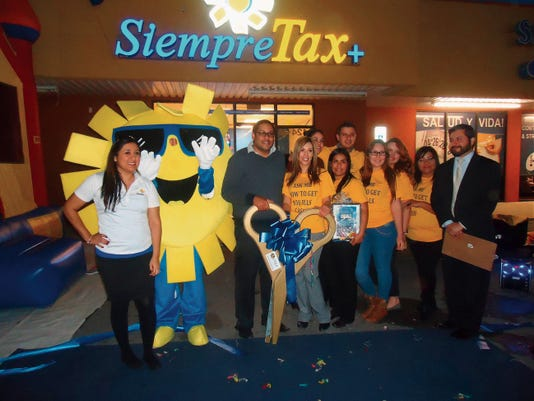 Siempre Tax employees celebrate after the ribbon cutting of a new office.