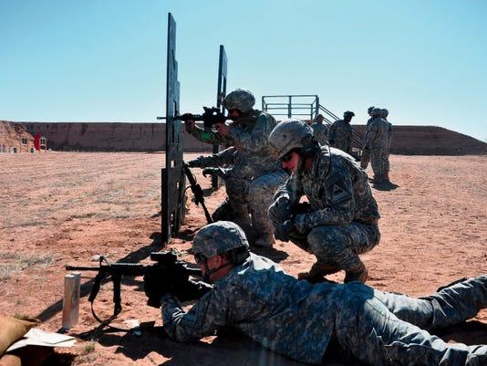 2nd Brigade commander Col. Chuck Masaracchia coaches a soldier on proper firing techniques.