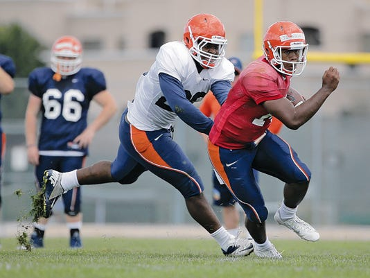 UTEP freshman quarterback Kavika Johnson, right, is chased by defensive back Justen Tatum during an Aug. 13 practice at Camp Ruidoso.
