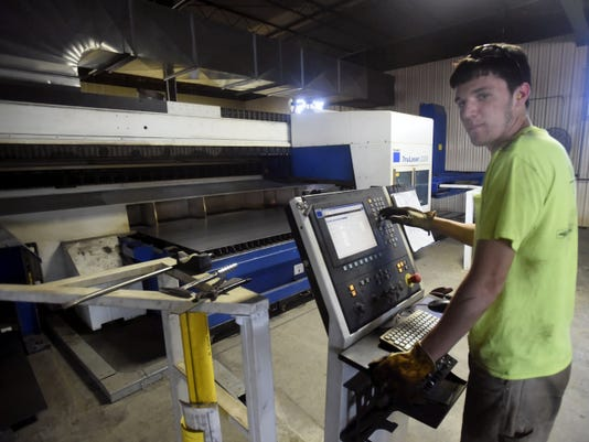 Logan Benton works a cutting laser machine Wednesday at YB Welding in Chambersburg. The facility at 1005 S. Main St. is expanding.