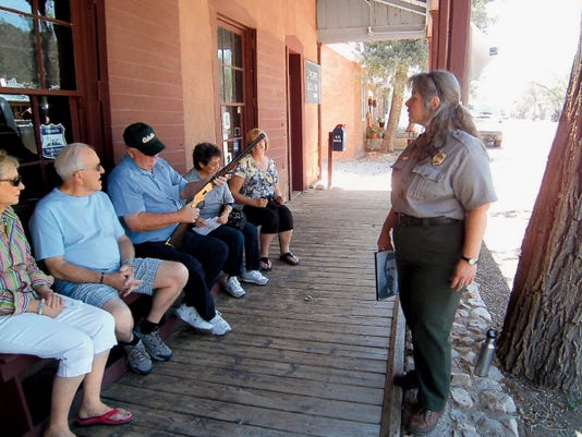 """You might have carried this Winchester rifle had you lived on the 'most dangerous street in America'.""  Ranger Sandy James, DCA of Lincoln Historic Sites, in uniform, begins her Ranger talk on the porch of the Tunstall Store Museum."