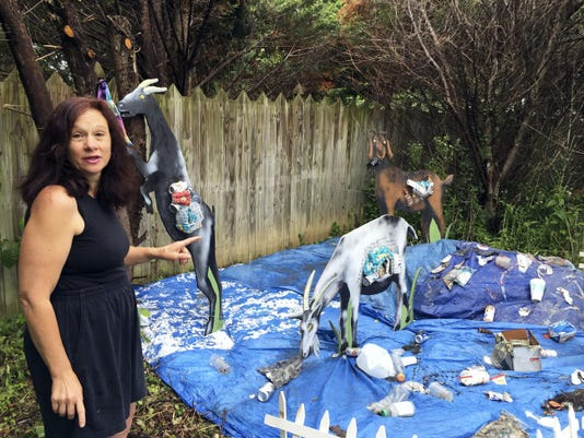 """Linda Apuzzo stands beside the """"Trash Goats,"""" a project completed by her and her niece to raise public awareness about trash."""