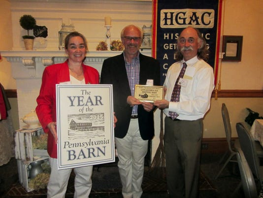 HGAC awards Littlestown veterinary Hospital Barn Preservation Award: Historic Preservation Society of Gettysburg-Adams County (HGAC) Preservation Committee Chair Curt Musselman, right, awarded Littlestown Veterinary Hospital owners Dr. Julie Holland, left, and Dr. Gary Kubala with its 2015 Barn Preservation Award at its Annual Meeting last month, as part of their Barn Preservation Project and Grant Program. The circa 1860-80 Littlestown Veterinary Hospital Barn, situated at 5010 Baltimore Pike, Littlestown, was on the brink of collapse in 1997. It was purchased by Willis and Denise Myers in 1998, who gave the barn the structural support it needed, and repaired and replaced rotted and missing beams and brought the structure back from the brink of collapse. In 2008 the current owners purchased the barn and continued with the preservation process, at the same time converting the structure into a veterinary hospital. Today the barn is a multi-use facility that is home to not only the veterinary hospital but also a pet grooming business, the Jaycees, a place for storage for the Littlestown Historical Society, and a worship center.