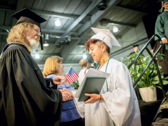 York County School of Technology professor Kim Oberdick, left, hands graduate Makenzie Weaver an American flag in recognition of her future service in the U.S. Armed Forces after Weaver crossed the stage with her diploma during commencement at the York Expo Center on Tuesday.