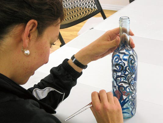 "Morgan Metcalf creates a masterpiece with a recycled wine bottle, one of the activities featured in ""Transformations,"" an adults-only evening of special activities, wine, beer and food treats from 5:30 to 9 p.m. today at city museums on Main Street Downtown."
