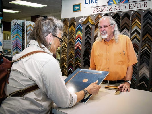 Jett Loe--Sun-News   Silversmith and oil painter Angie Sears talks with Frame & Art owner Ron Saltzman in his store. Sears has been a frequent customer of the art supply and framing store for almost 8 years.