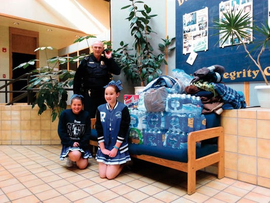 Last week, the Ruidoso Middle School Cheerleaders donated water, power bars, blankets and other important items to the Ruidoso Police Department. Representing the cheerleaders were Alysa Sagarayoshimyra and Arika Rivas, pictured with Ruidoso Police Chief Joe Magill.