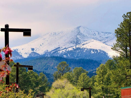 The storm shrouded Sierra Blanca Peak off and on over the weekend and left the mountain covered with snow, while the village received rain and trees continued to blossom.
