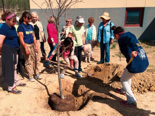 Ruidoso Middle School Student Council members shovel dirt into the new school tree presented by the Garden Club.