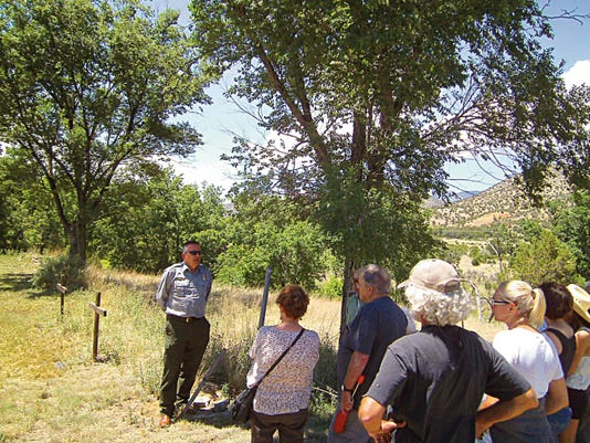 """Who's buried here? Ranger Murray Arrowsmith, DCA, of Lincoln Historic Sites (in uniform) reveals exciting details of the little-known Tunstall Cemetery. """"But please don't step in the neighbor's back yard!"""""""