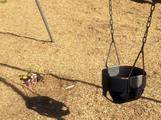 In this photo taken May 26, 2015, a stuffed animal and flowers sit near a swing in Wills Memorial Park in LaPlata, Md. A Maryland woman who was found pushing her dead son in a playground swing earlier this year has been indicted and charged with manslaughter and child abuse, authorities announced Monday. The Charles County, Md. State's Attorney's Office announced that Romechia Simms, 24, was arrested Saturday and faced an arraignment Monday morning. (AP Photo/Matthew Barakat)