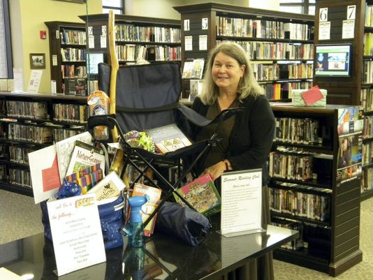 Ruth Potter, the winner of Guthrie Memorial Library's Adult Summer Reading Club, displays her grand prize. The 10th Annual Adult Reading Club attracted more than 407 participants and was a success.