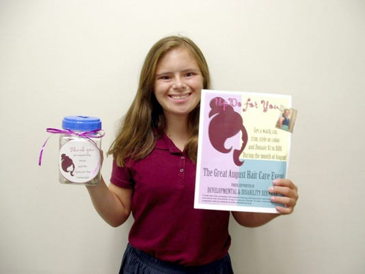 Emily Rakow holds posters and canisters for her UpDo for You Campaign to raise money for Developmental & Disability Services of Lebanon Valley.