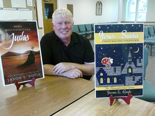 The Rev. Dr. Royle, pastor of St. Paul's United Church of Christ in Schaefferstown, poses inside the church with covers of the two books he has written.