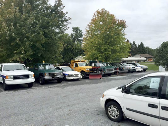 A mini-van owned by Lebanon County is parked across a line of city-owned vehicles in the Lebanon Municipal Building parking lot on South Eighth Street in preparation for Wednesday's auction of government property.